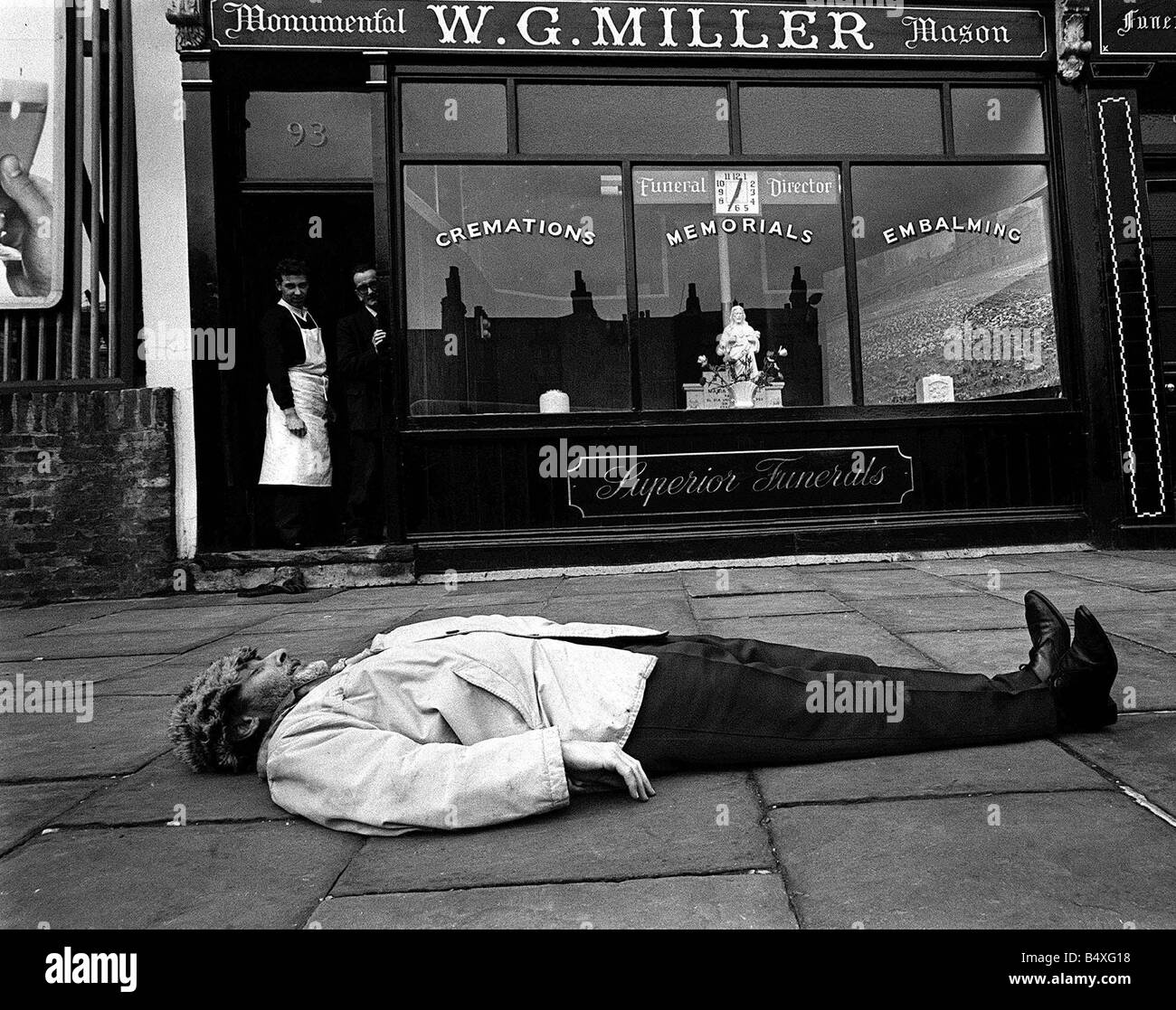 Spike Milligan comedian and author March 1963 prostrate on the pavement in front of Islington undertaker W G Miller - Stock Image