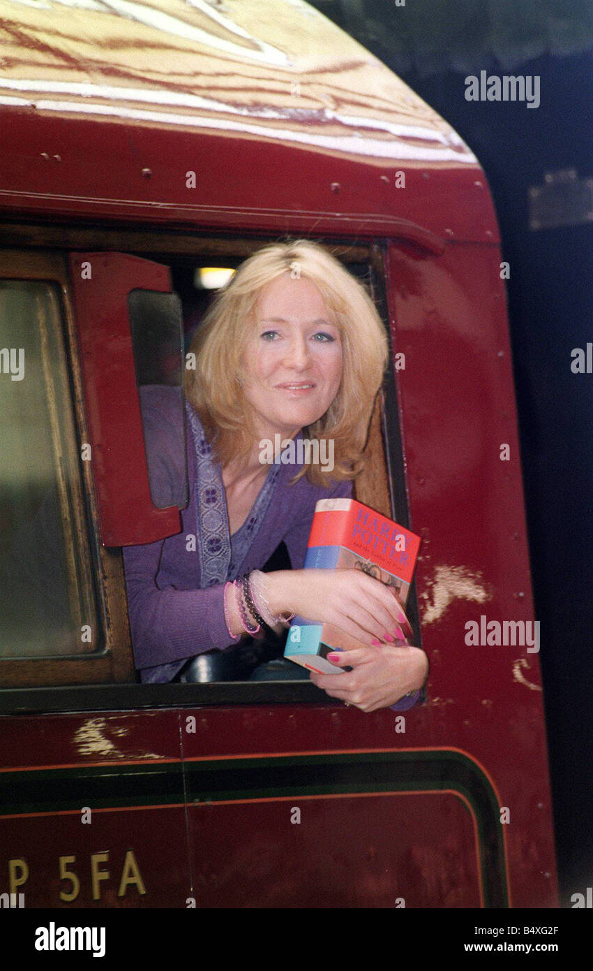 J K Rowling Author leans out of a steam train named Hogwarts Express at Kings Cross railway station in London holding - Stock Image