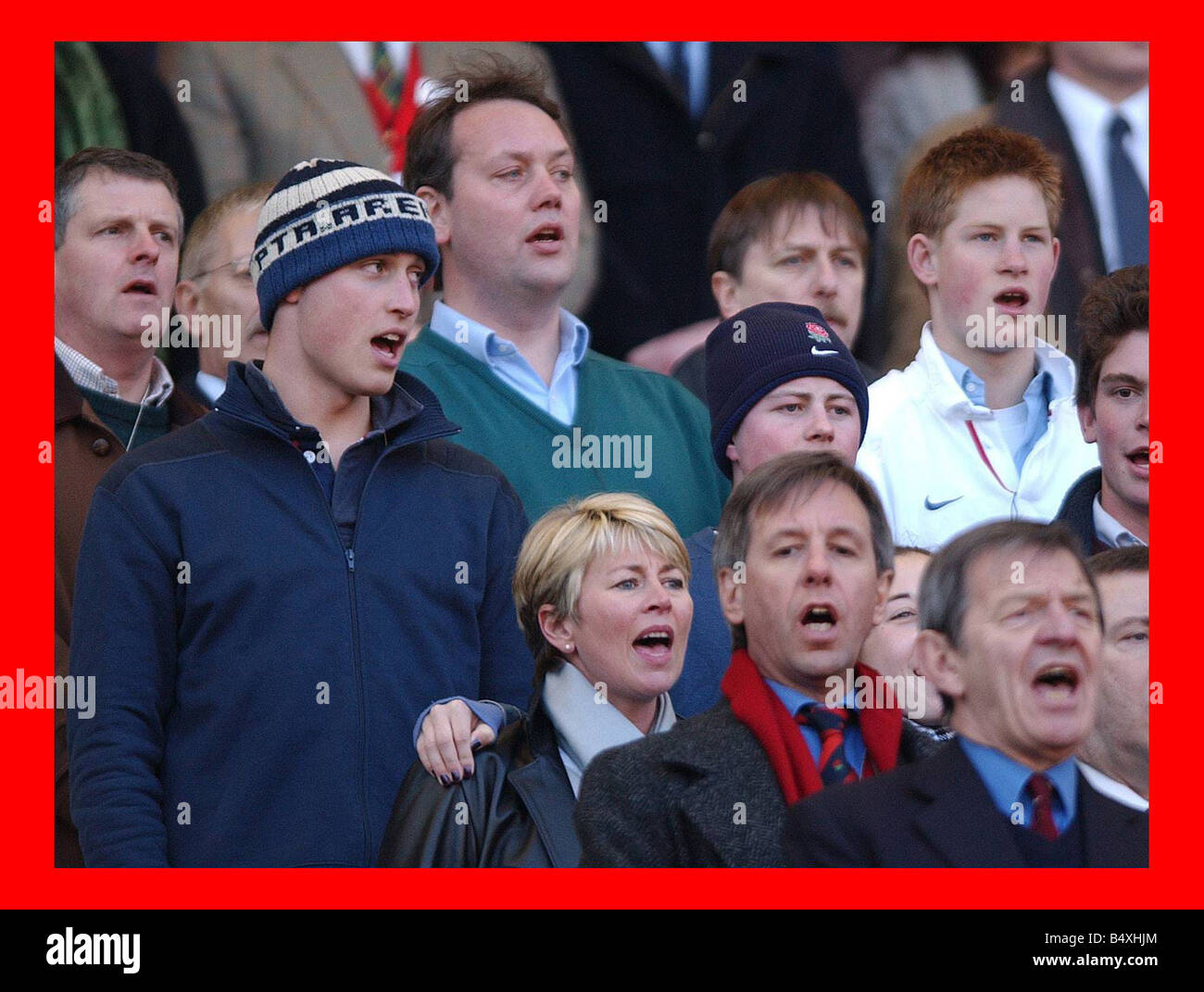 Prince William sings the National Anthem still wearing his wooly hat while his brother Harry does things correctly - Stock Image