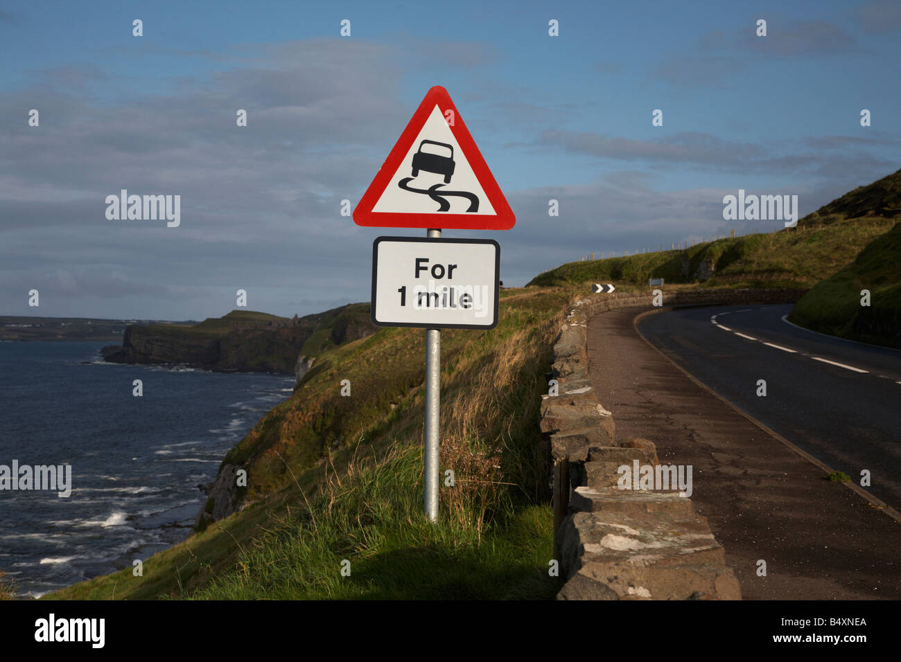 slippery road danger red warning triangle for 1 mile sign on the famous A2 north antrim causeway coastal road route - Stock Image