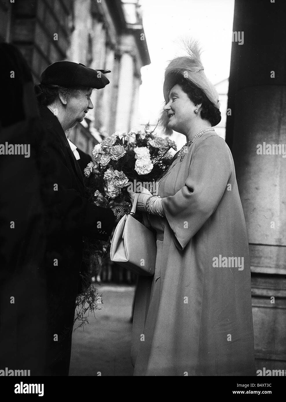 Queen Elizabeth now the Queen Mother receives a bouquet from Rose Riana 71 during her visit to Belfast 1950 Royalty - Stock Image