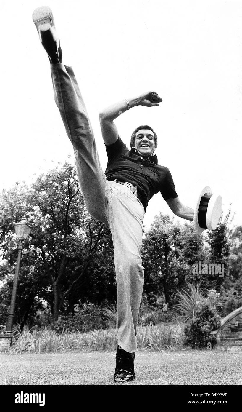 Frankie Vaughan singer and entertainer May 1974 kicking foot high up in air while holding straw boater hat - Stock Image