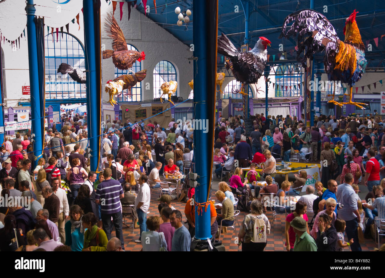 Crowds of people wander sit and browse stalls in the Market Hall during Abergavenny Food Festival - Stock Image