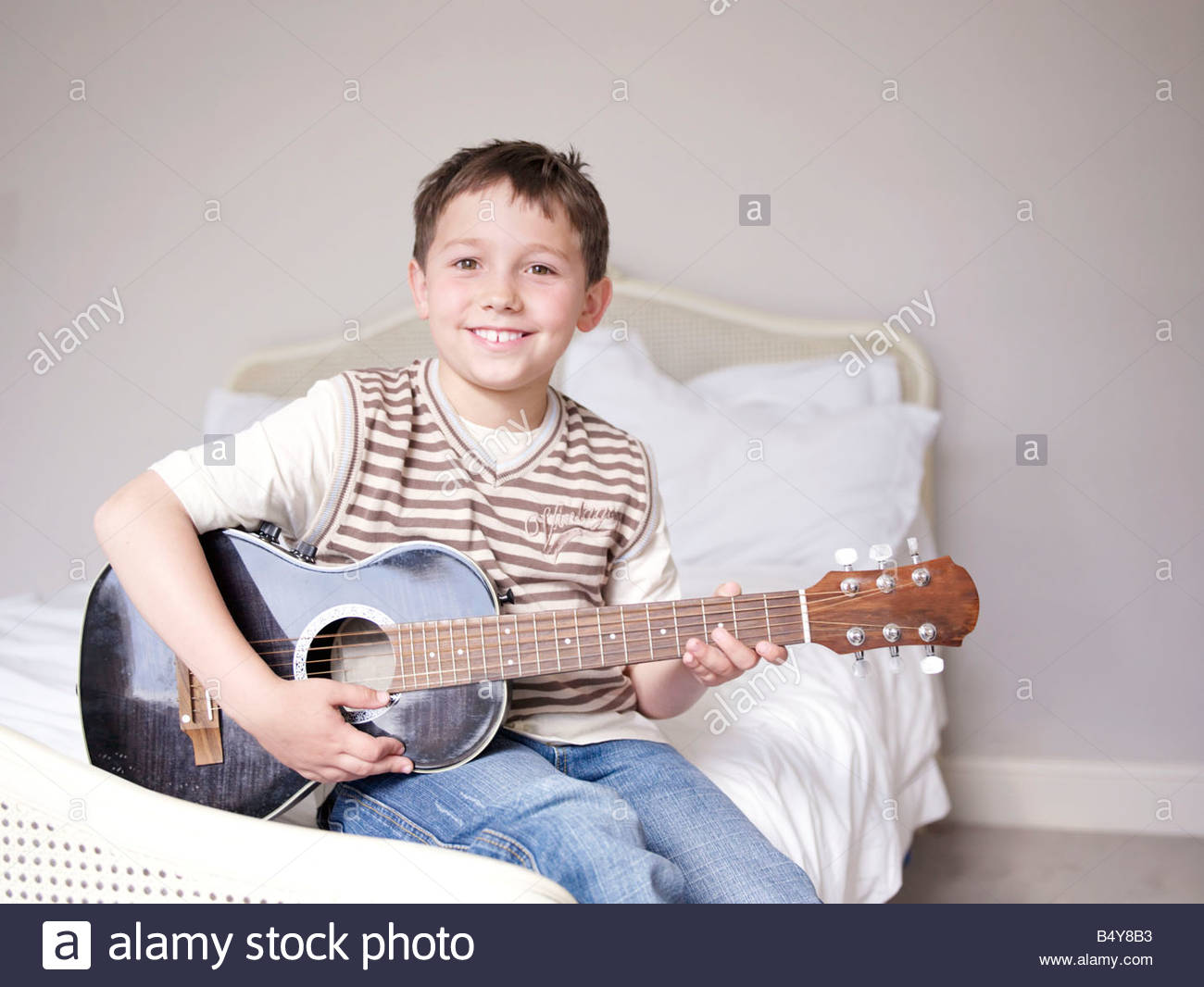 Young boy sitting on bed playing guitar Stock Photo