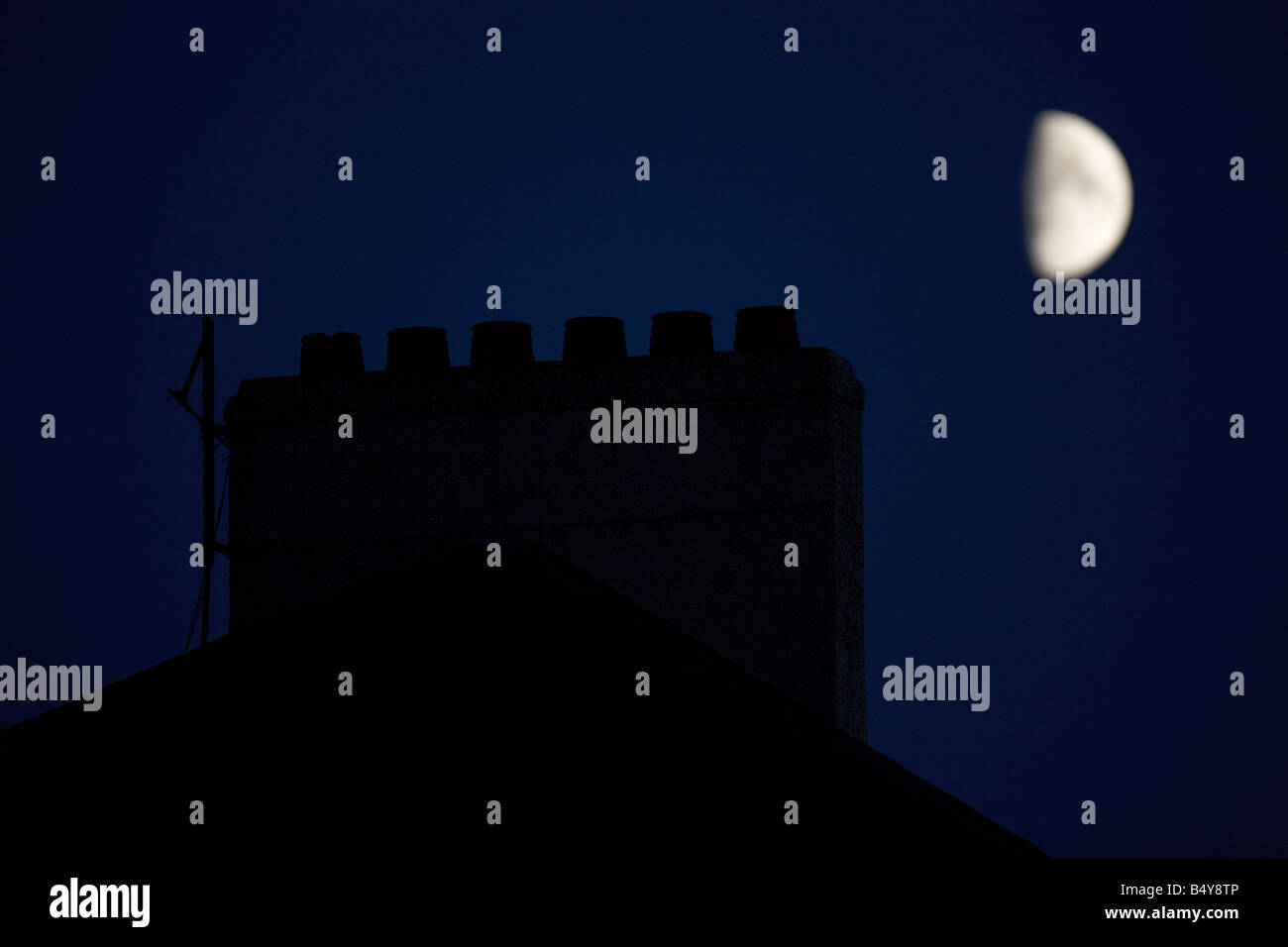 partial half moon rising over victorian chimney pot stack at night - Stock Image