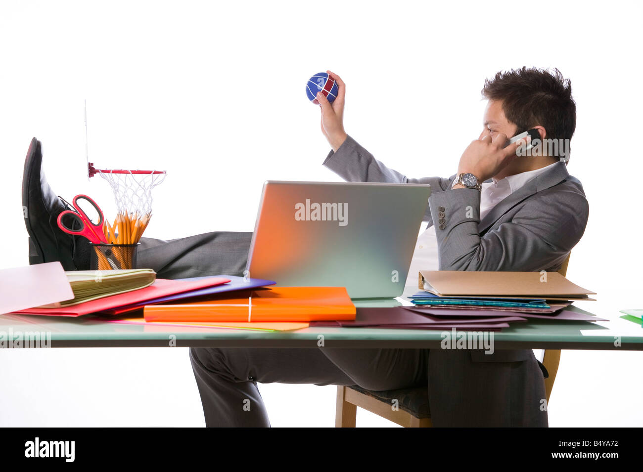 Busy businessman playing office basketball and talking on a phone - Stock Image
