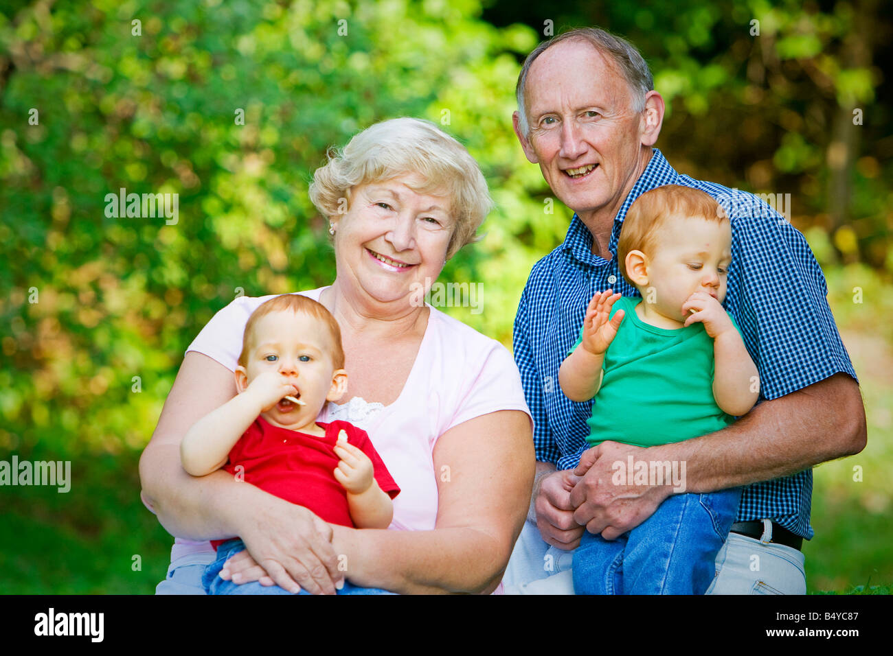 Holding redheaded twin grandsons with focus on happy grandparents - Stock Image