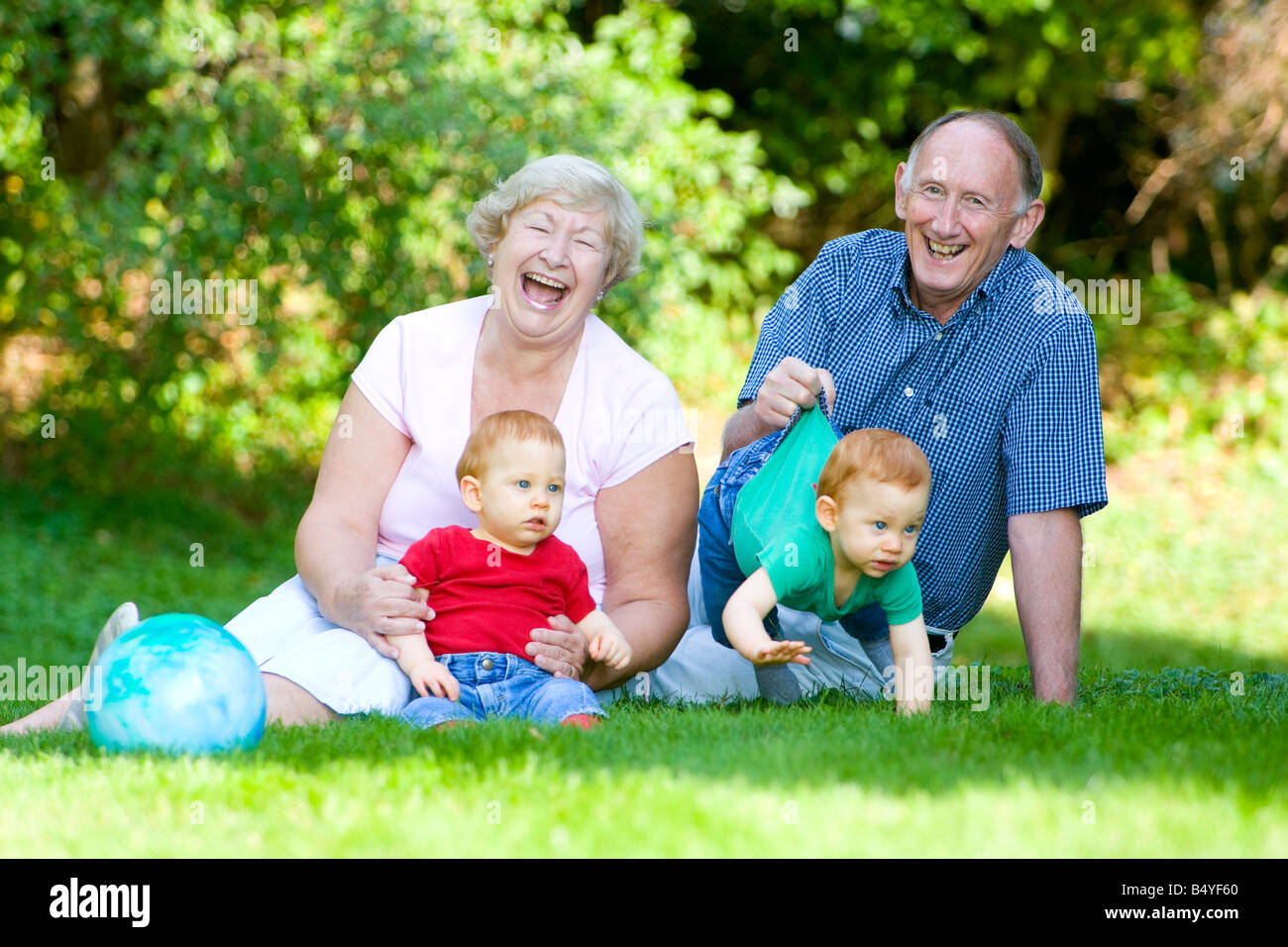 Playing with redheaded twin grandsons with focus on laughing grandparents - Stock Image