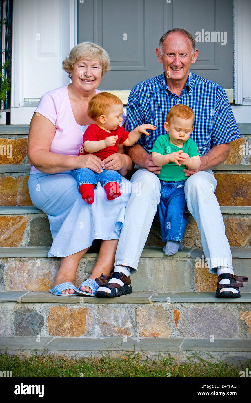 Happy handsome grandparents with twin grandsons outdoor portrait - Stock Image