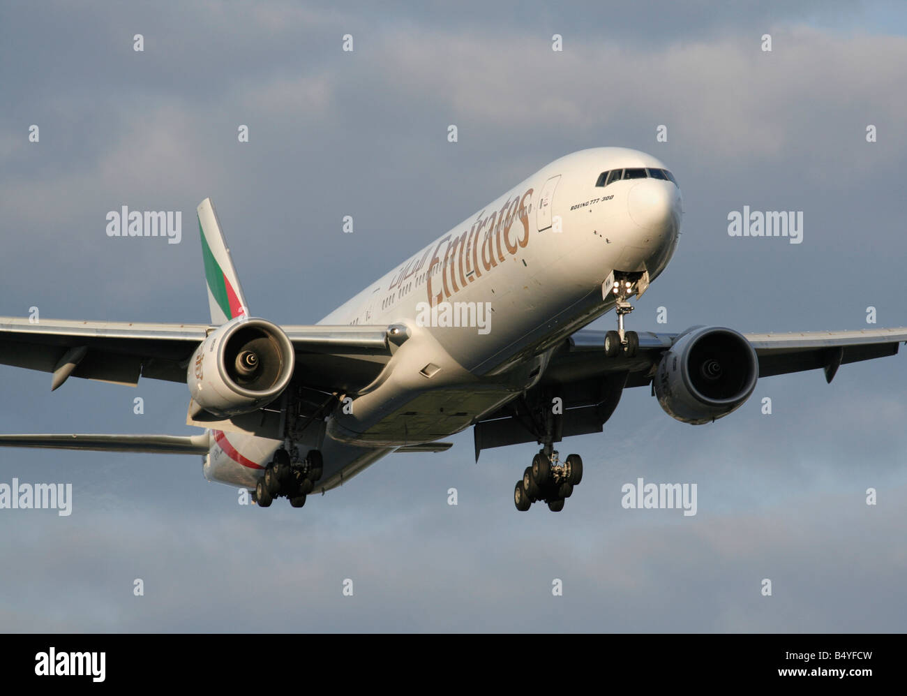 Emirates Boeing 777-300 landing at sunset - Stock Image
