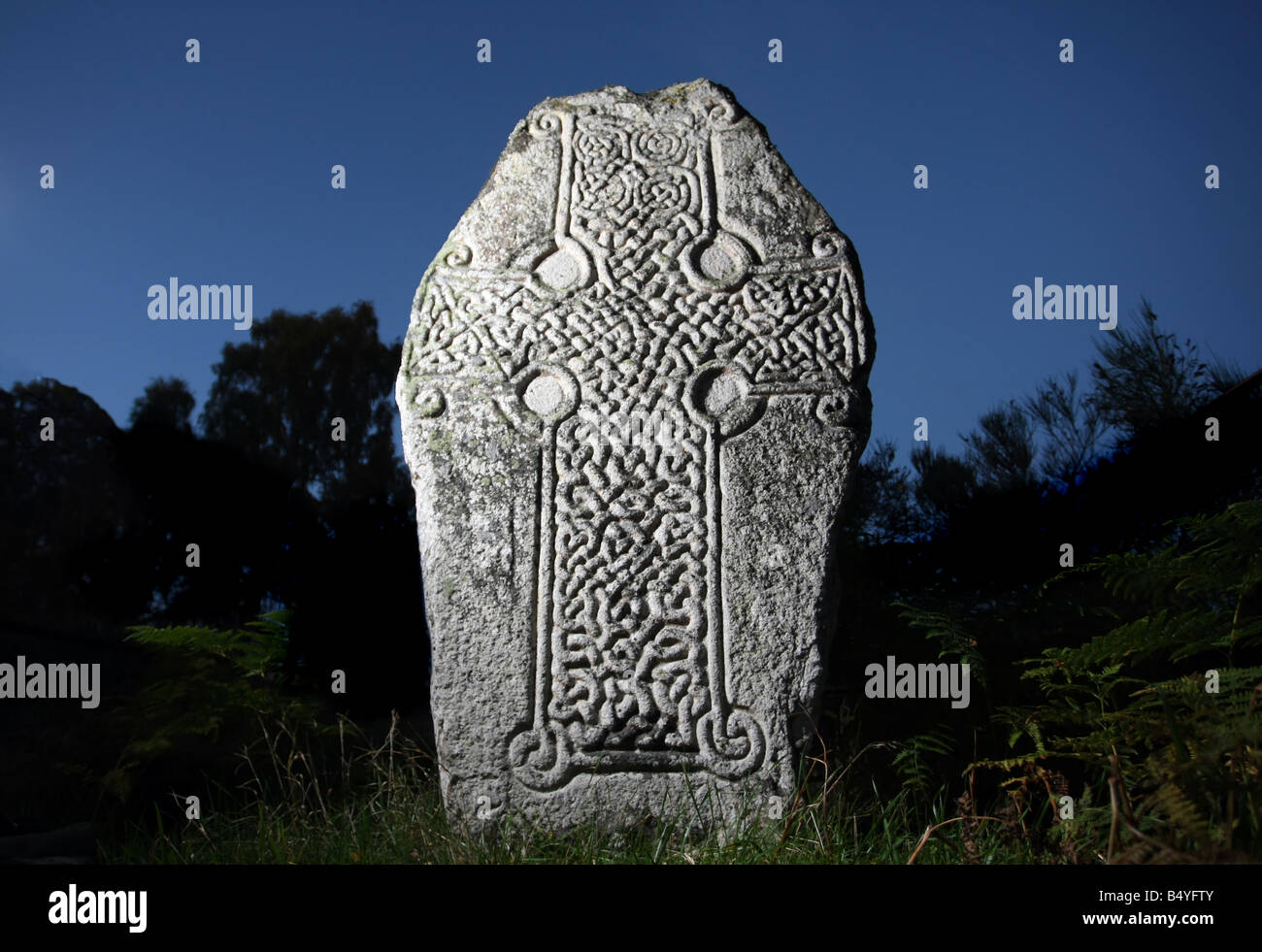 Ancient stone slab with carved Celtic Cross design, on the shores of Loch Kinord in Aberdeenshire, Scotland, UK - Stock Image