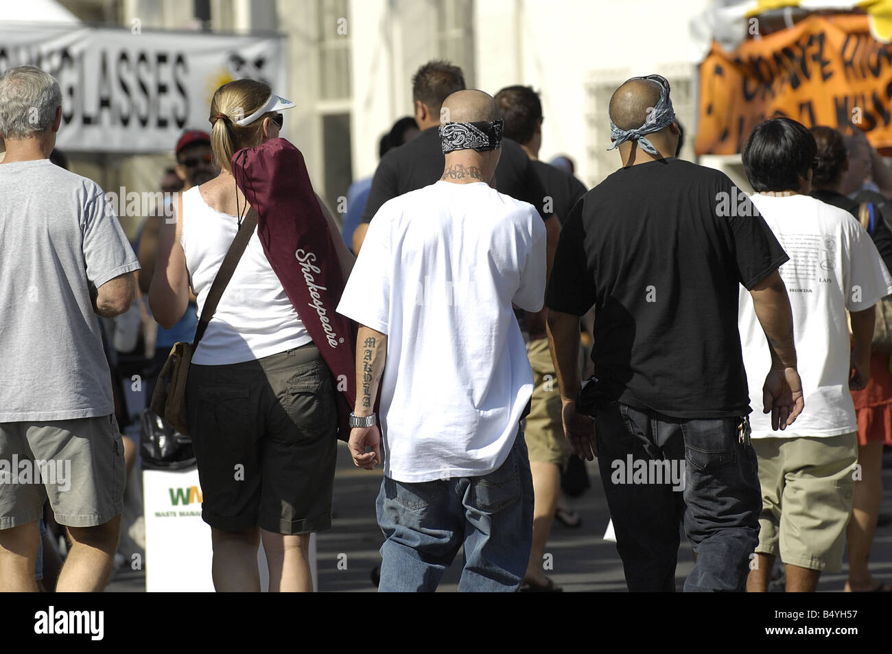 Suspected street gang members walk through a crowded street fair - Stock Image
