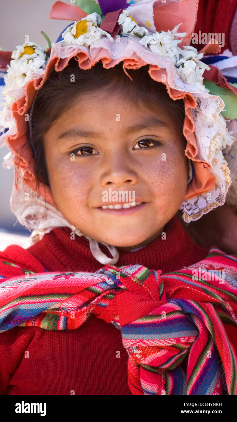 Little Peruvian girl wearing a traditional native Andean bonnet and shawl and smiling prettily. - Stock Image