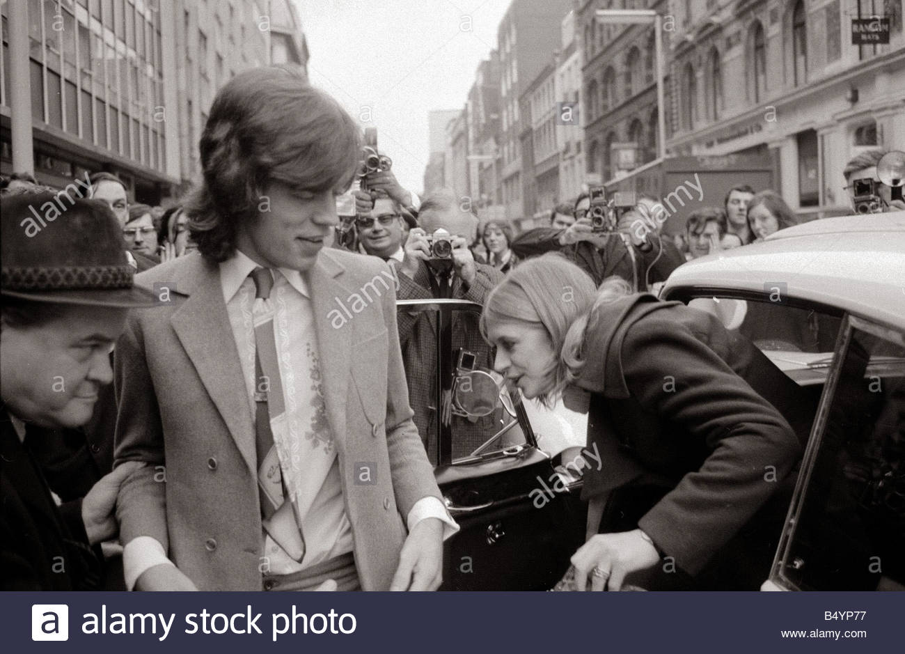 London January 1970 Lead singer of the Rolling Stones pop group Mick Jagger and girlfriend Marianne Faithfull arrive - Stock Image