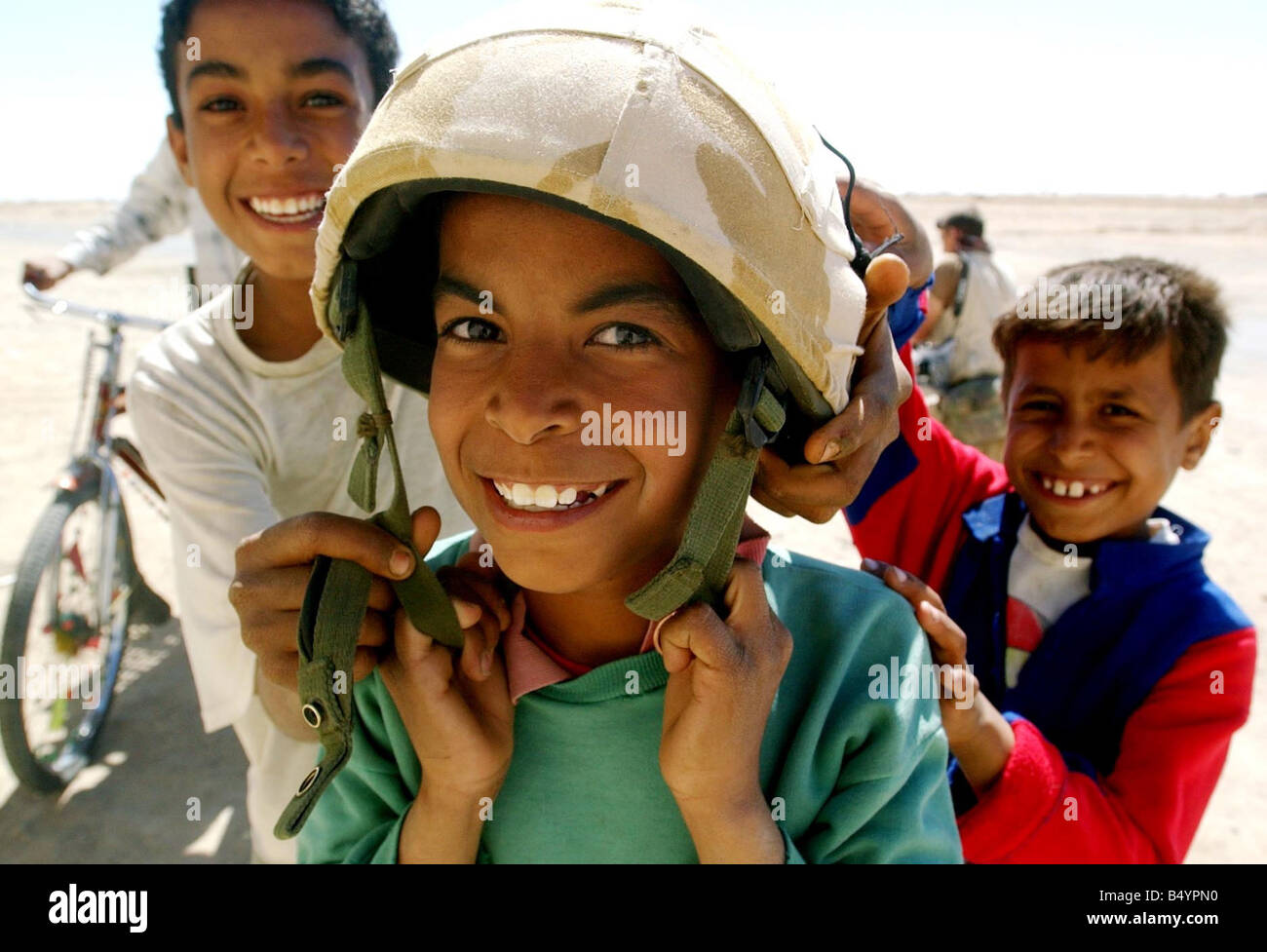 CHILDREN FOOL AROUND April 2003 WITH A SOLDIERS HELMET IN IRAQ everettselected - Stock Image