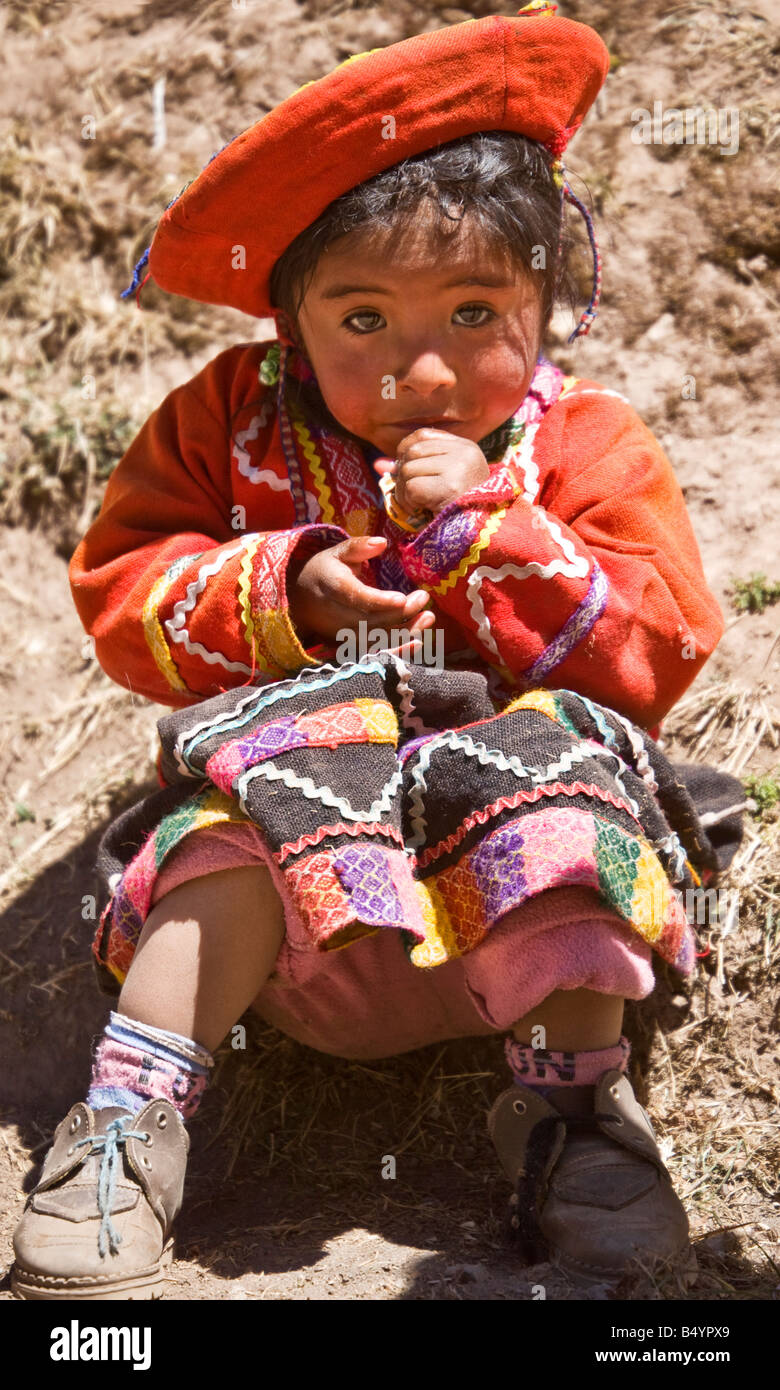 Small Peruvian girl toddler wearing traditional national native Andean costume or dress holds out her hand shyly - Stock Image