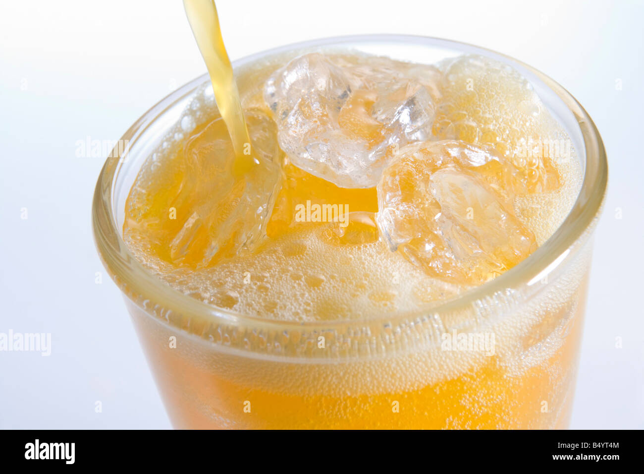 Pouring Orangeade Into A Glass Of Ice - Stock Image