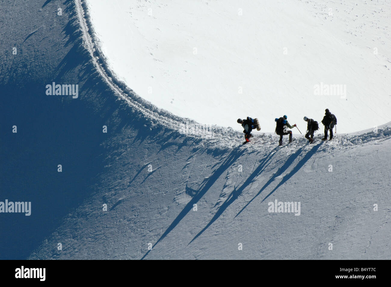 Mountain climbers ascend a tricky snow covered ridge on Mont Blanc in the French Alps Stock Photo