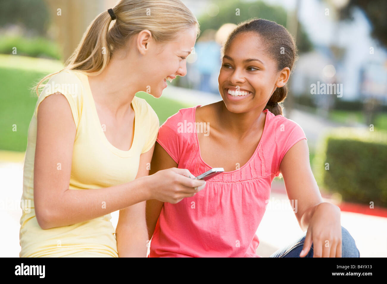 Teenage Girls Sitting Outside Playing With Mobile Phone Stock Photo