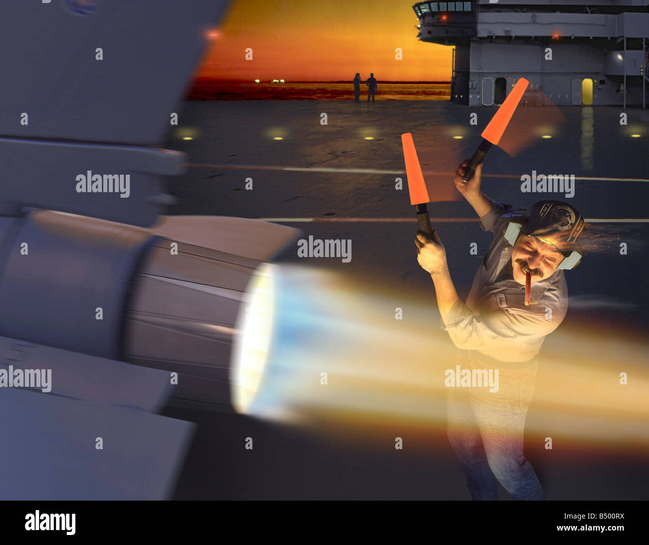 A man with marshaling lights on the deck of an aircraft carrier lights his cigar on the afterburner flames of a Stock Photo