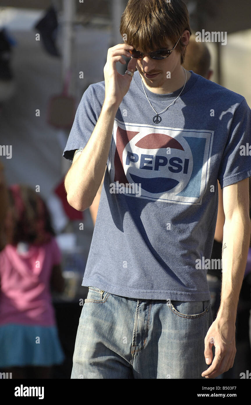 A young man in his twenties wearing jeans a Pepsi shirt and a peace symbol necklace - Stock Image