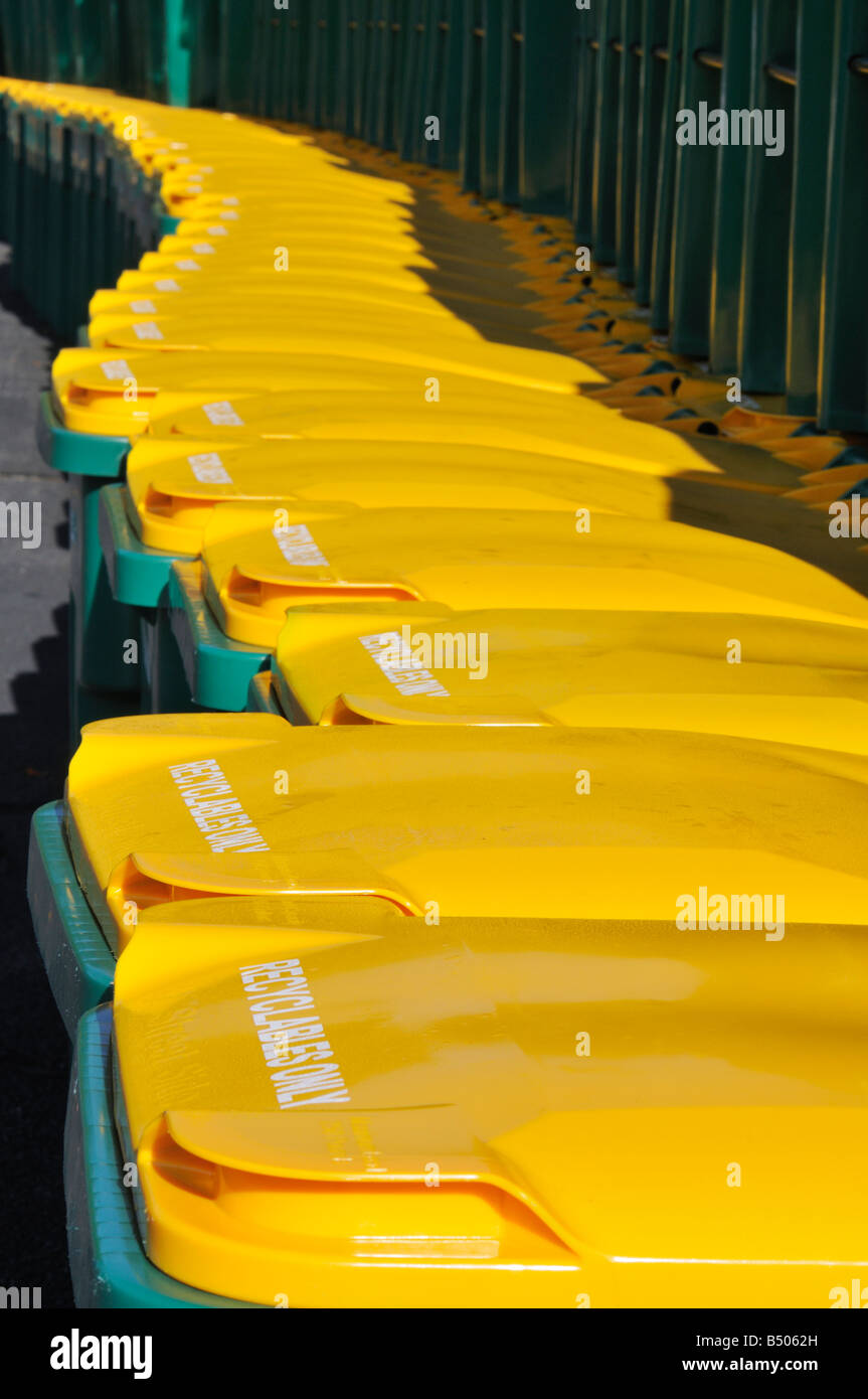 Lots of recycling bins or wheelie bins lined up in a row with bright yellow lids Stock Photo