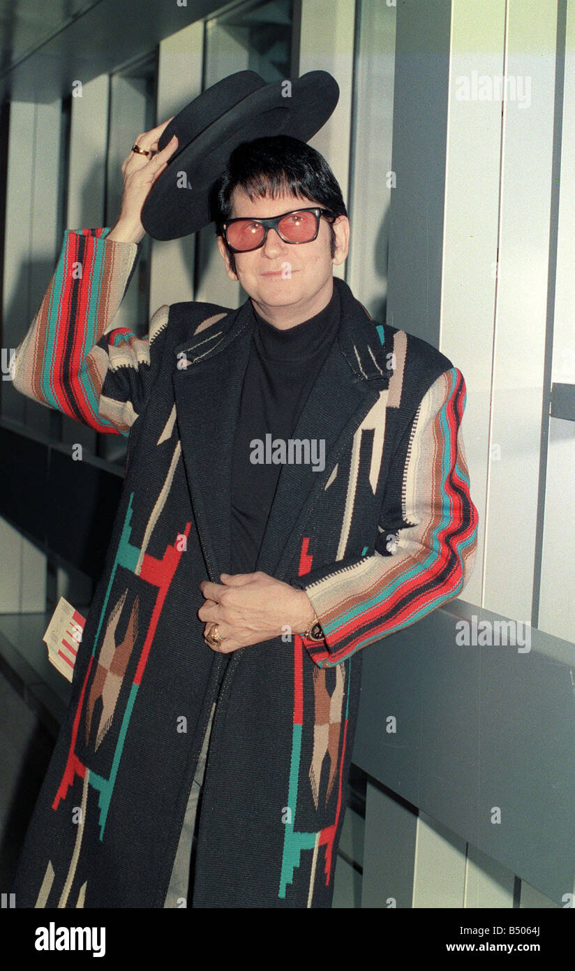 Roy Orbison at Heathrow Airport November 1988 in multi coloured coat holding hat in the air Stock Photo