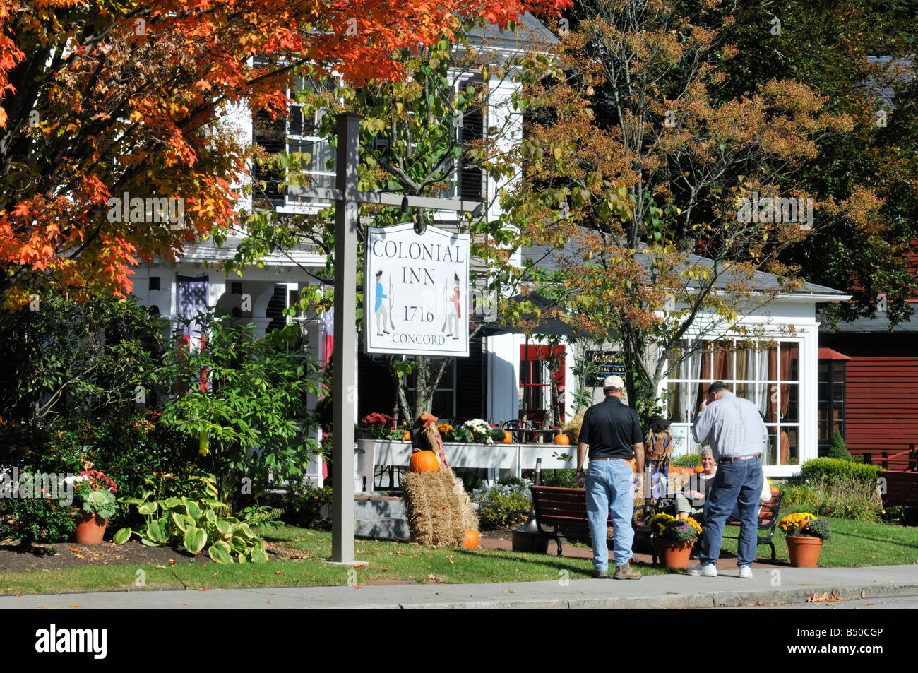 Exterior of Colonial Inn, circa 1716 in Historic Concord Massachusetts in fall with people, pumpkins, sign and building - Stock Image