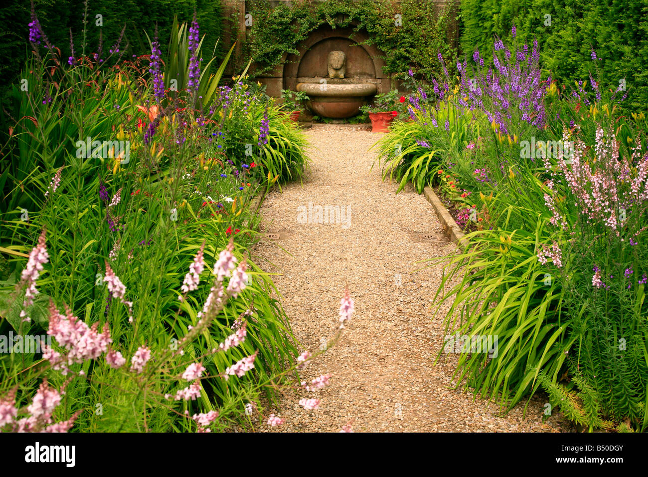 Lions head fountain in a beautiful country cottage garden. - Stock Image