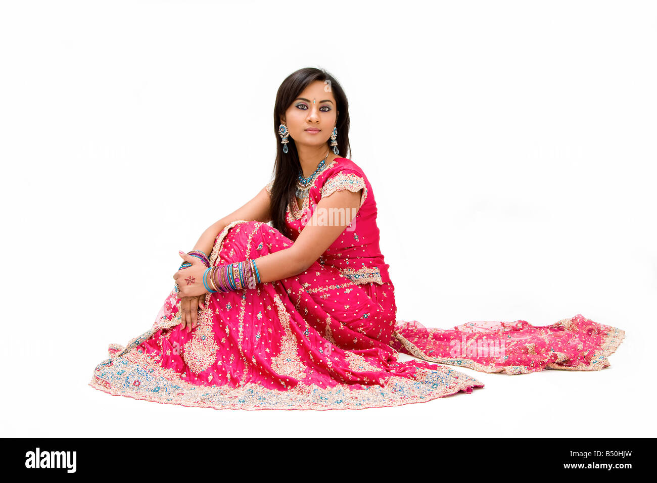 Beautiful Bangali bride in colorful dress sitting isolated - Stock Image