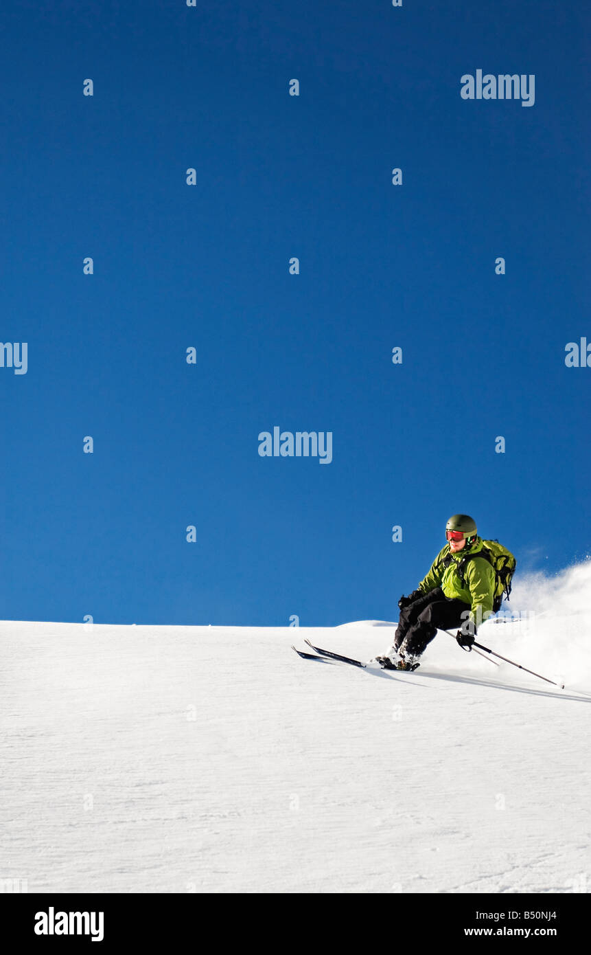 Low angle view of a young man skiing Alps Switzerland - Stock Image