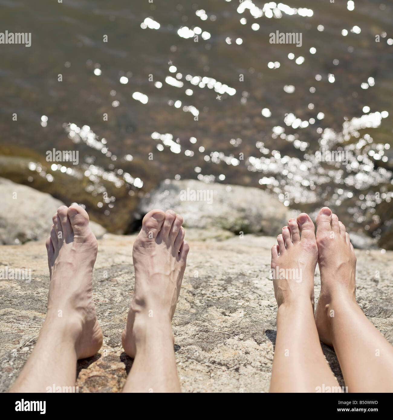 Close up of a couple s legs on the coast - Stock Image