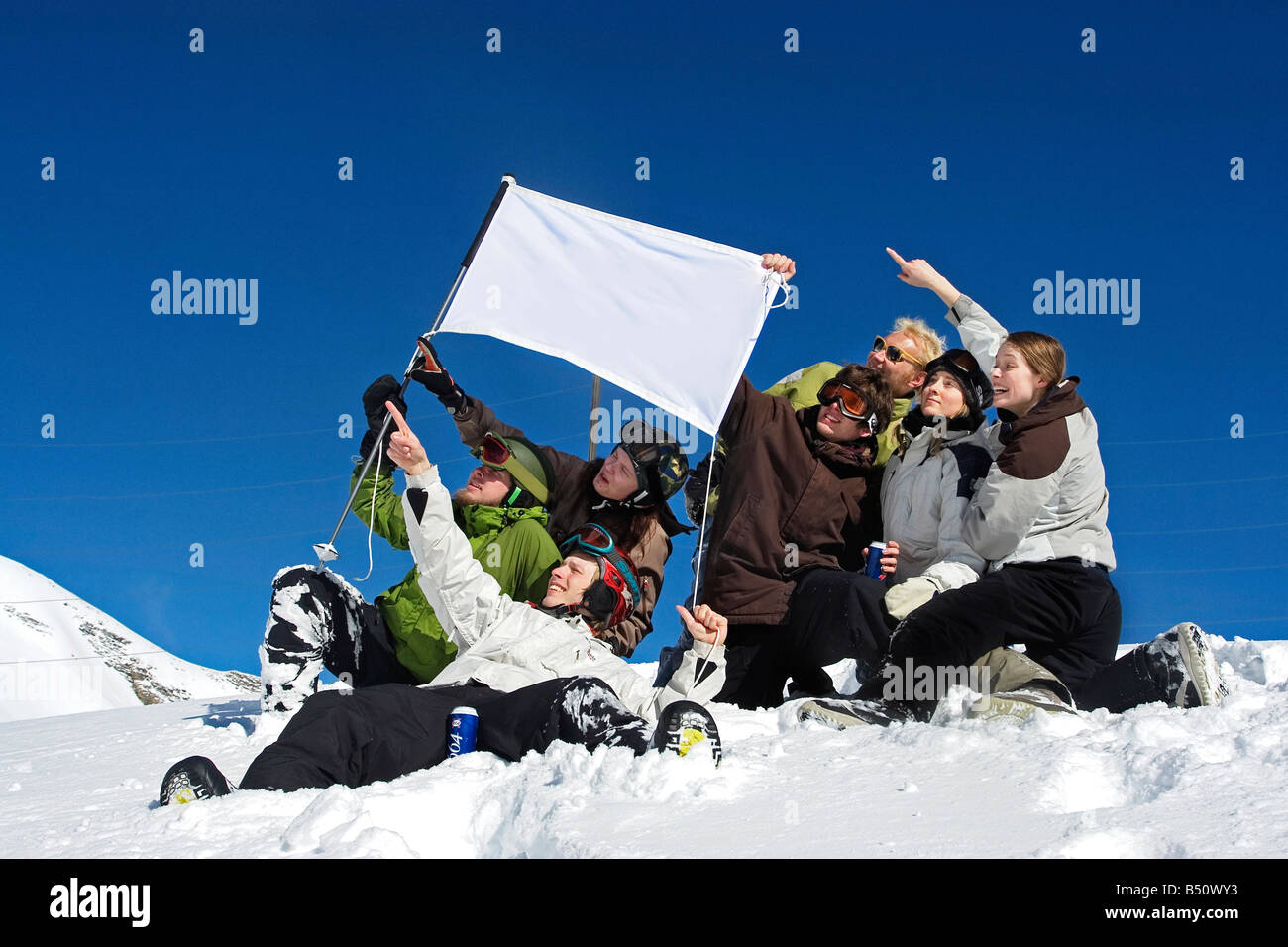 Low angle view of a group of people with a flag on the top of a mountainan Alps Switzerland - Stock Image