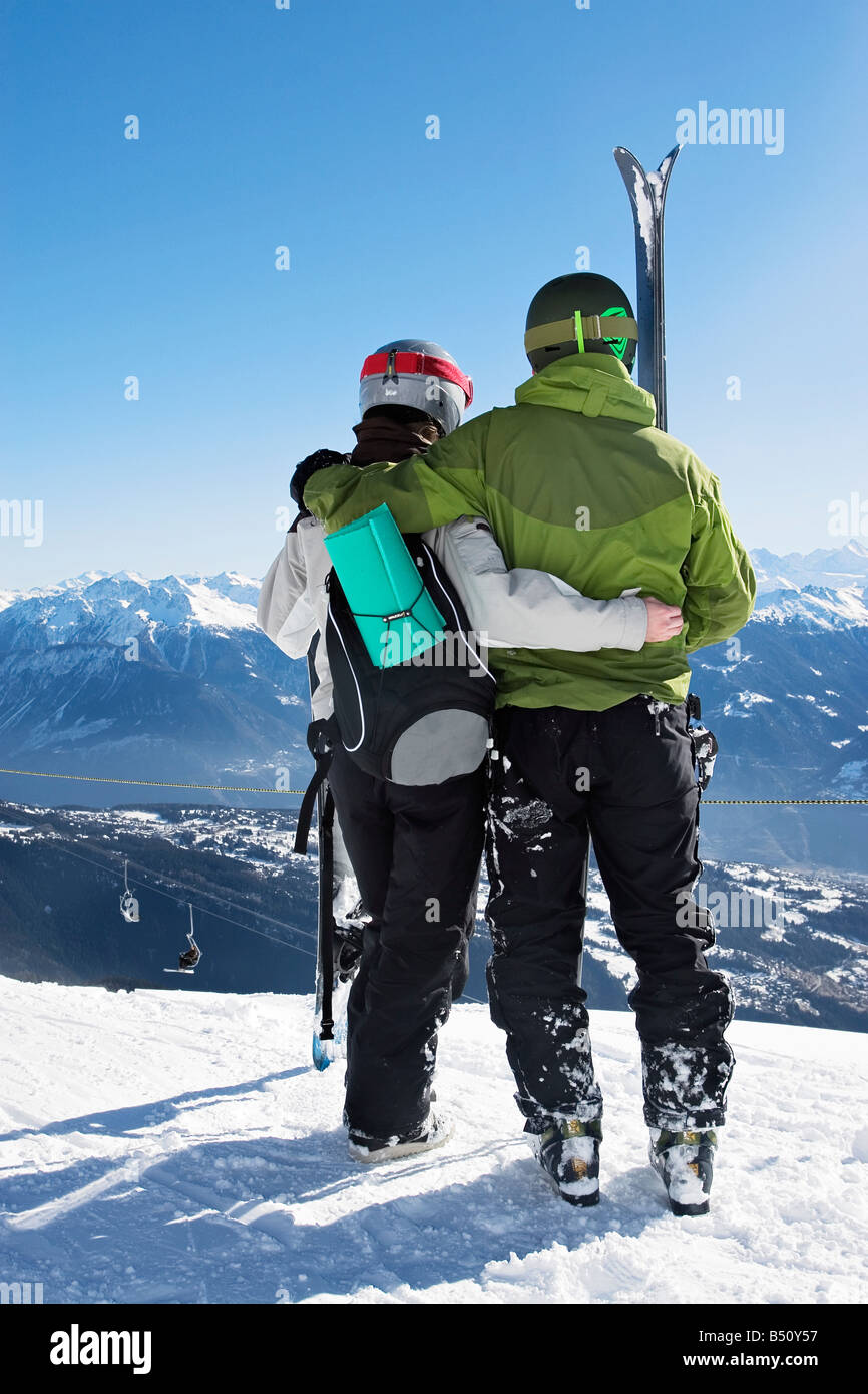 Rear view of a young couple standing with downhill skis and a snowboardan Alps Switzerland - Stock Image