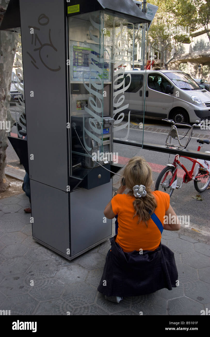 Woman on phone Telefonica telephone kiosk barcelona spain - Stock Image