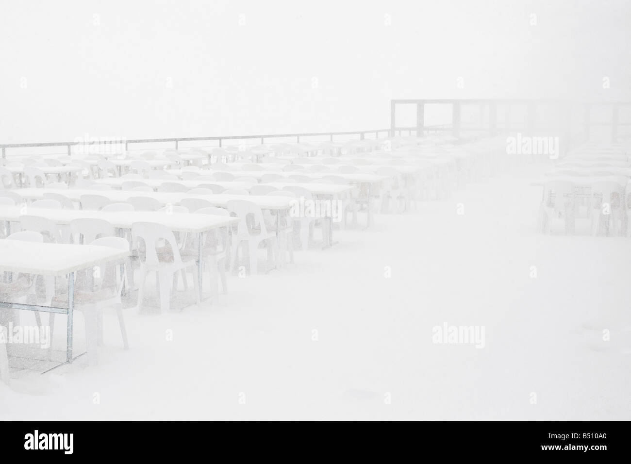 Snow covered tables and chairs in a restaurant Switzerland - Stock Image
