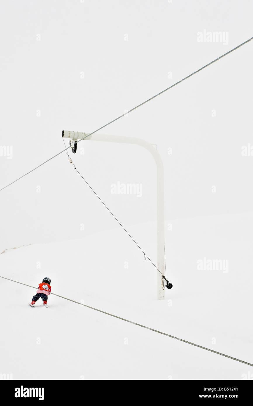 Rear view of a boy using ski lift Alps Switzerland - Stock Image