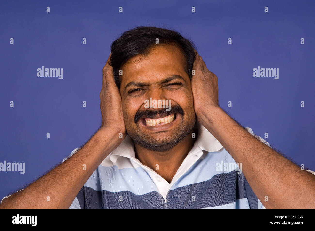 Indian man hands covering ears Stock Photo