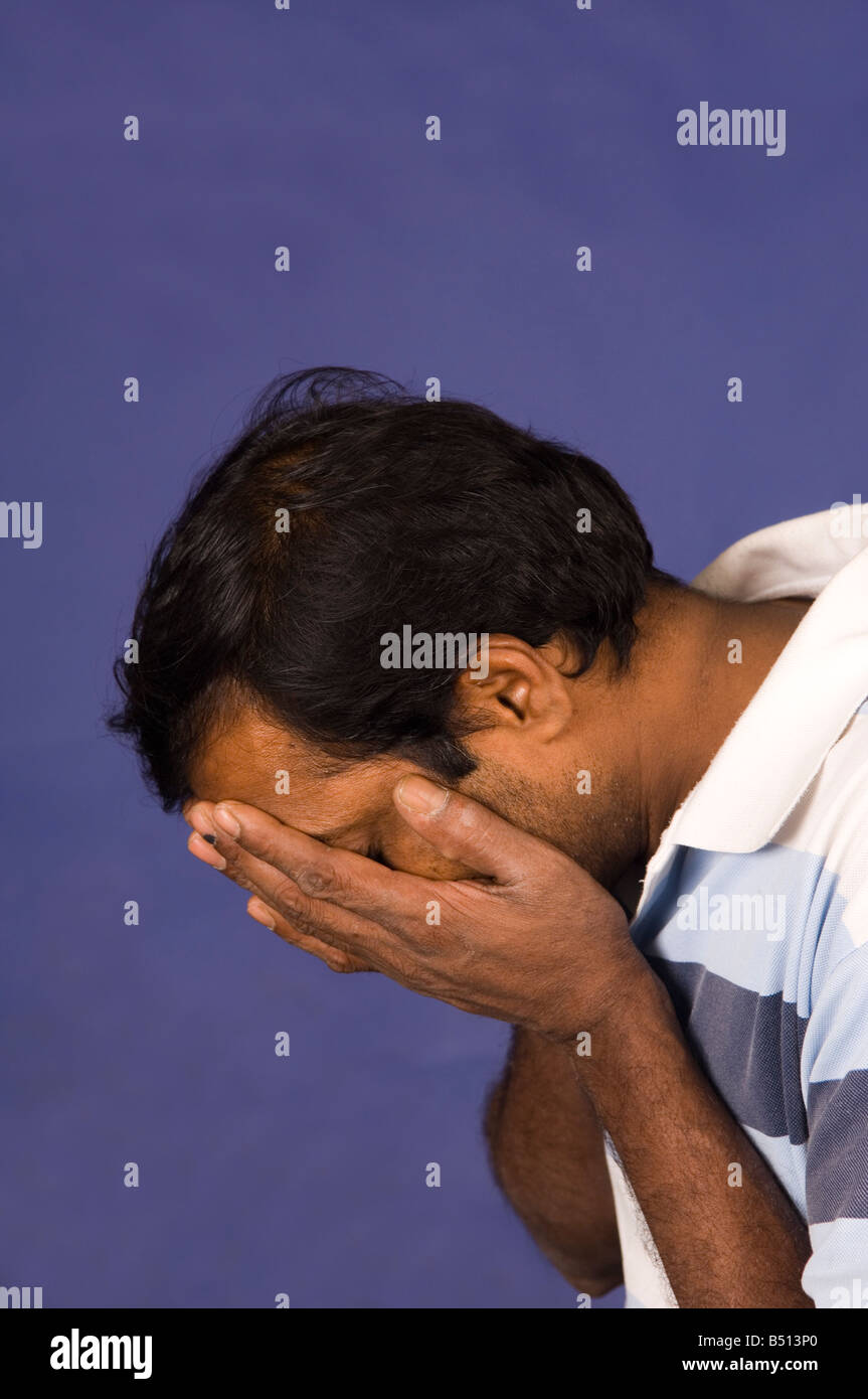 Mature Indian man head in hands Stock Photo