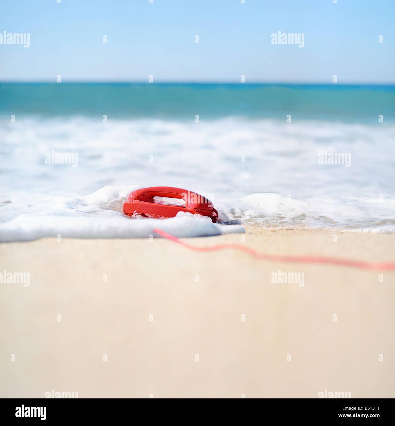 Landline telephone in surf on the beach - Stock Image