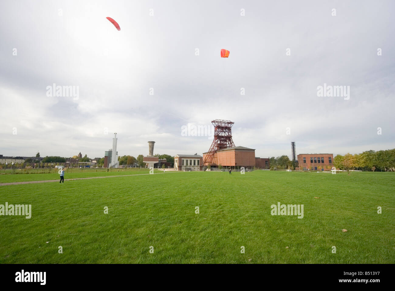 men with power kites - action in an old industrial area with a shaft tower - Stock Image