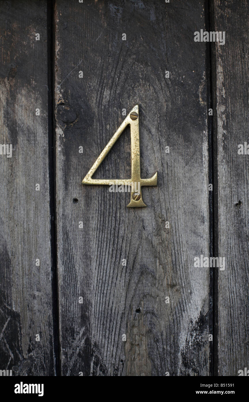 Brass numeral No 4 on shed door Nidderdale, North Yorkshire - Stock Image