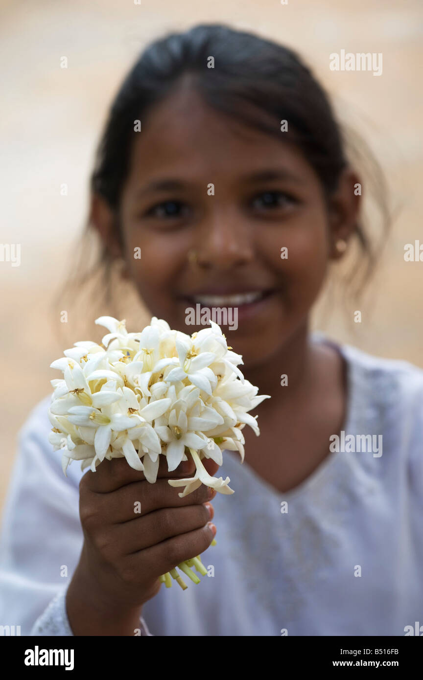 Indian girl holding flowers from Indian Cork tree - Stock Image