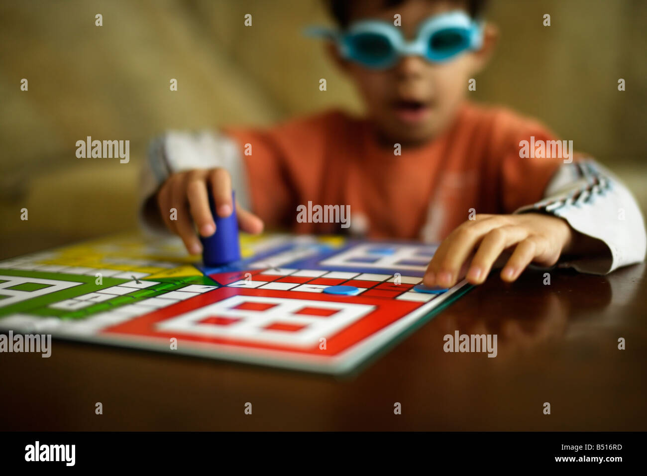 Six year old boy plays Ludo whilst wearing swimming goggles Stock Photo