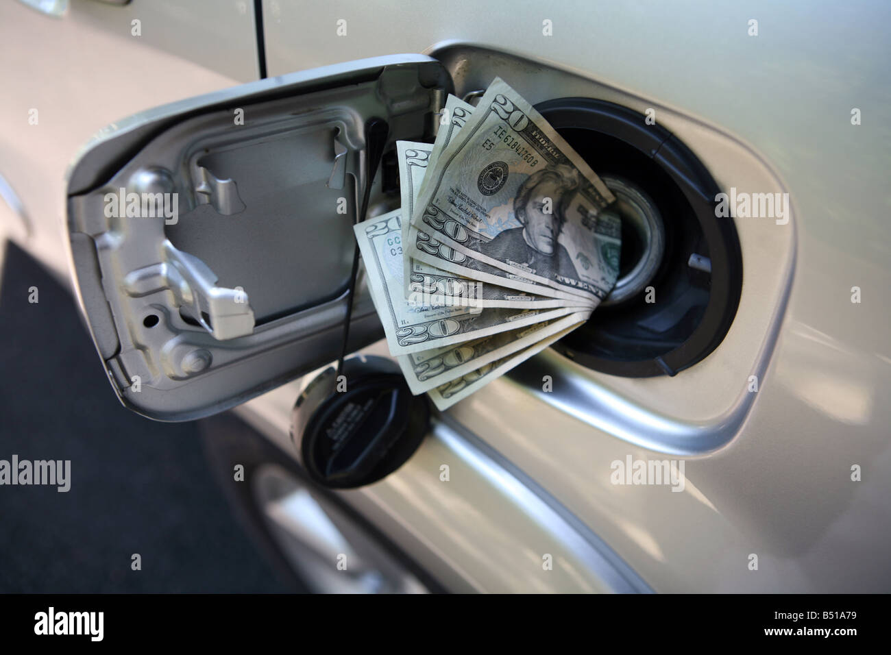 Money down the fuel tank - Stock Image