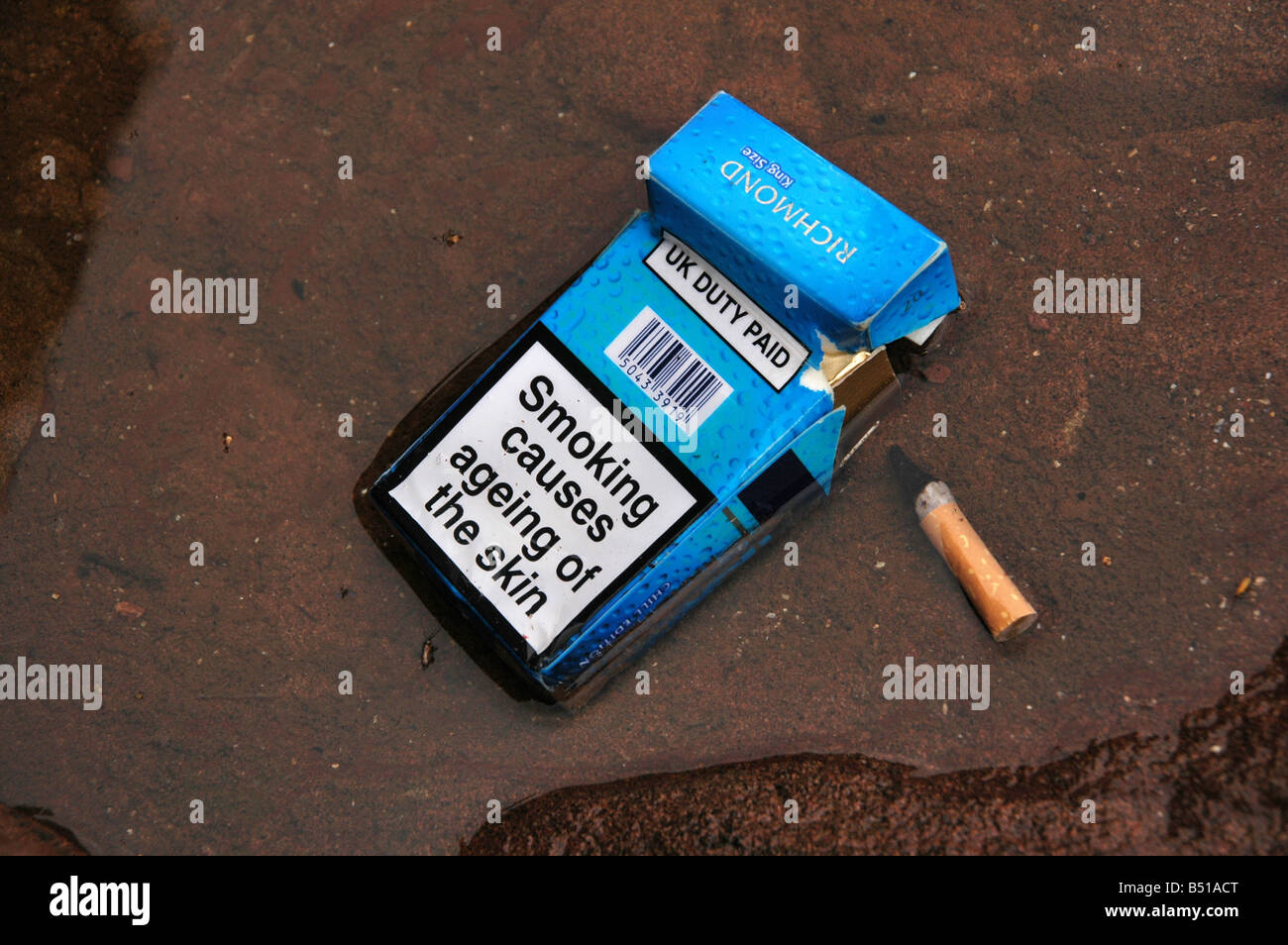 An empty packet of cigarettes with the warning of  'smoking causes ageing of the skin' with a smoked stub - Stock Image