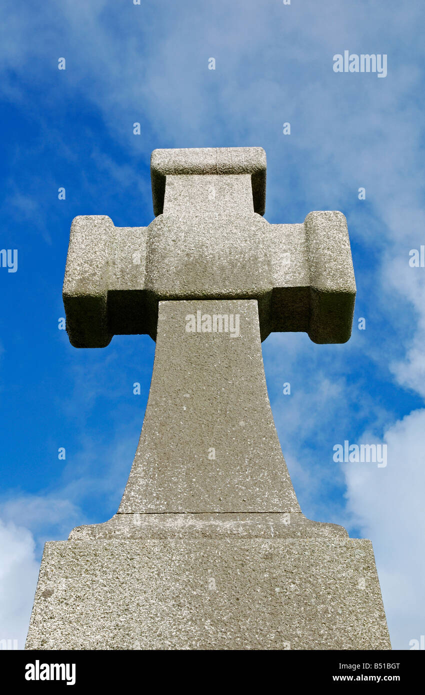 a large granite stone cross against a blue sky - Stock Image