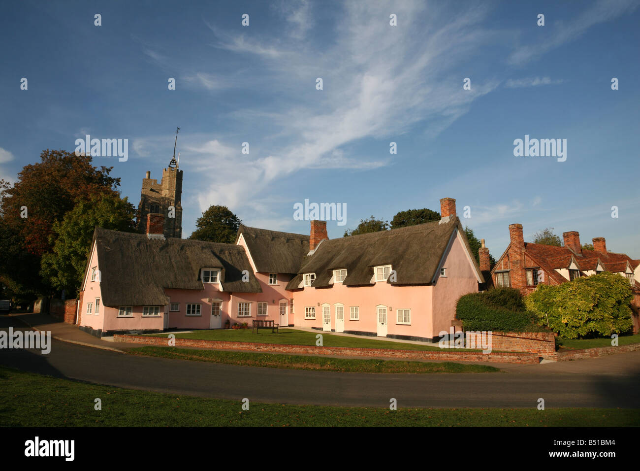 Cavendish in Suffolk showing traditional pink thatched cottages and village green - Stock Image
