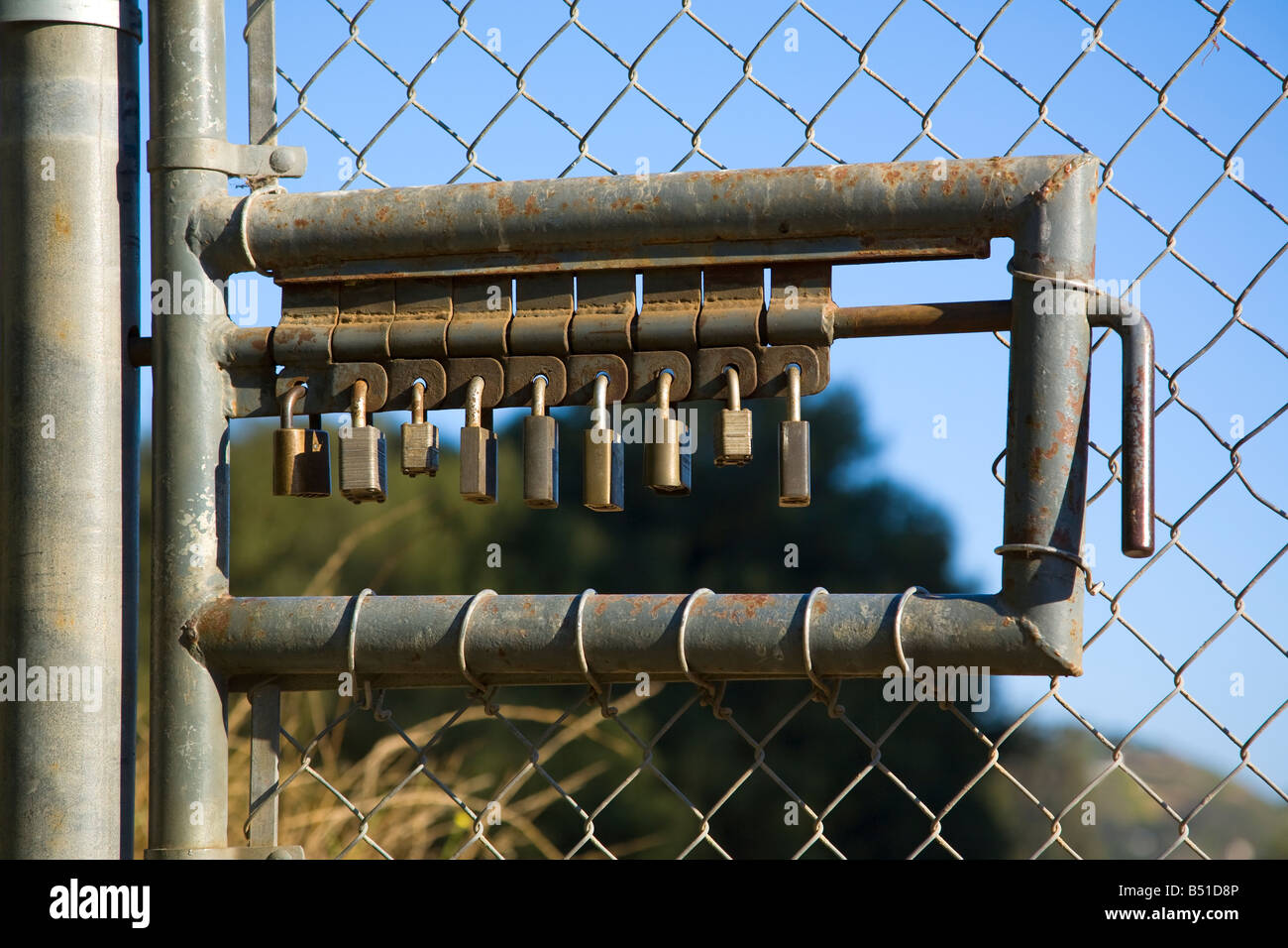 A true lock down concept, 9 pad locks make this gate to a restricted area a very secure barrier Stock Photo