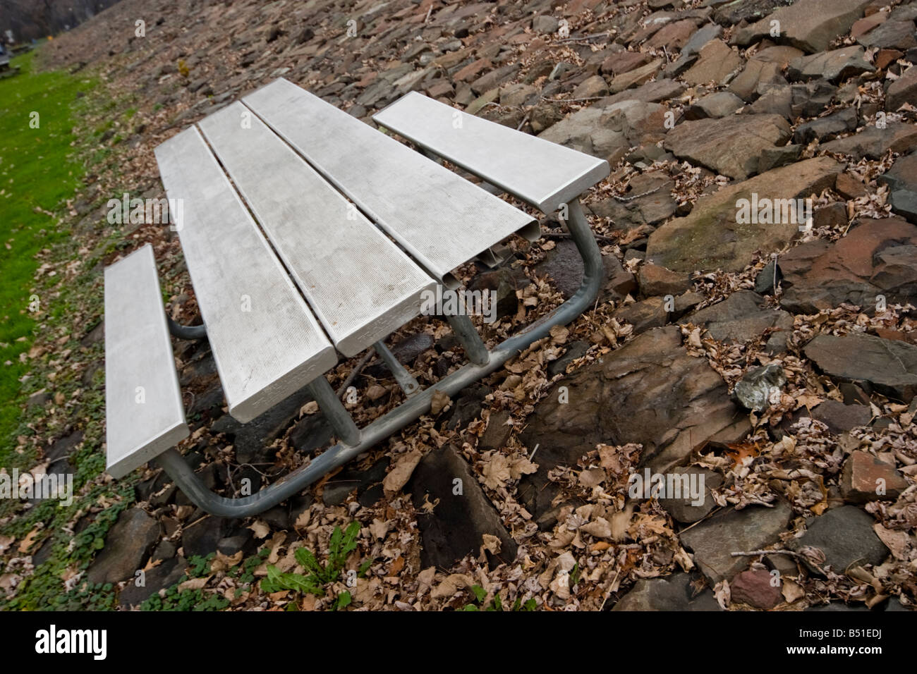 Metal picnic table setting on a rock surface by the edge of a road in a park & Metal picnic table setting on a rock surface by the edge of a road ...